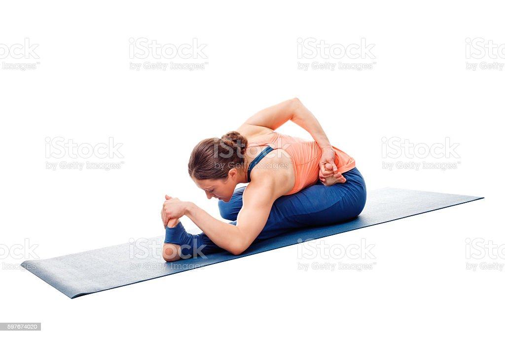 Woman doing Ashtanga Vinyasa Yoga asana Ardha baddha padma pasch stock photo