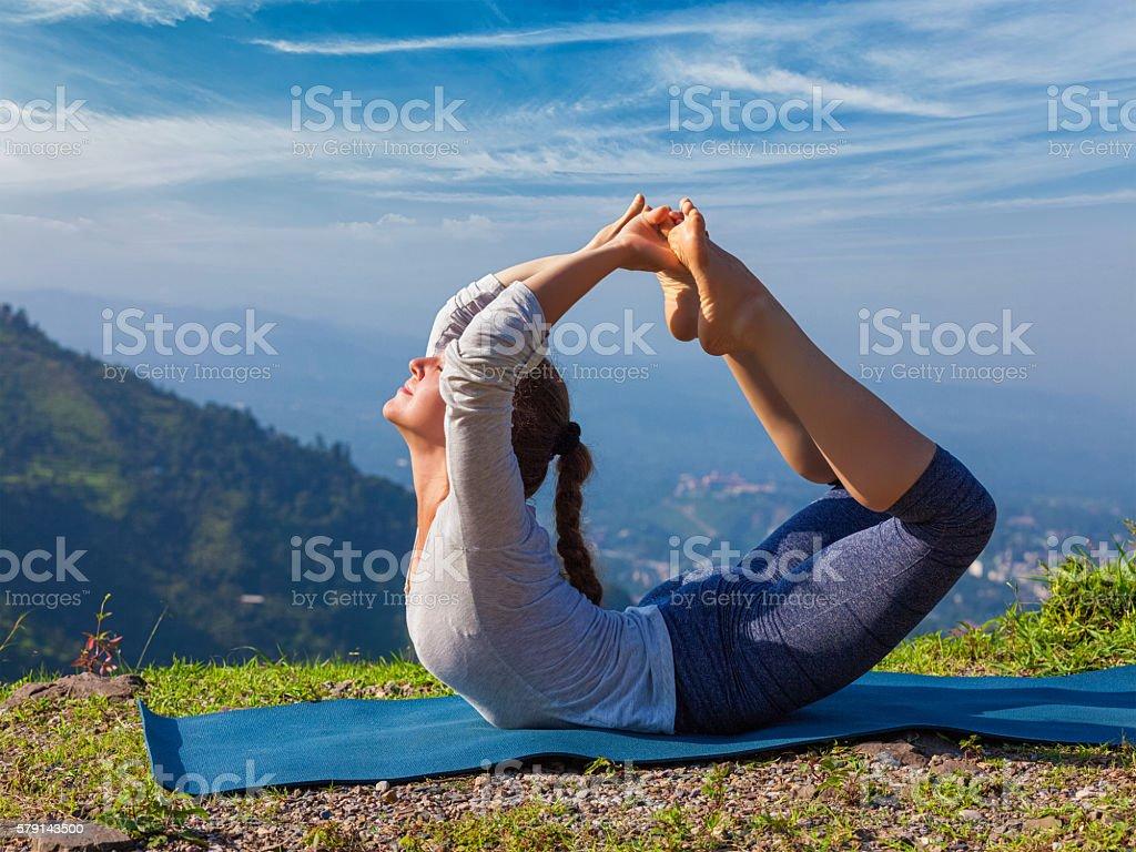 Woman doing Ashtanga Vinyasa Yoga asana Dhanurasana - bow pose stock photo