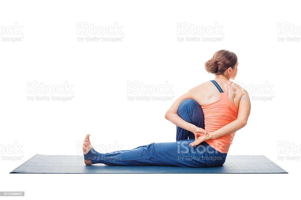 Woman doing Ashtanga Vinyasa Yoga asana Marichyasana C stock photo
