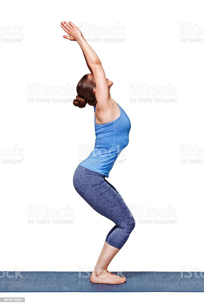 Woman doing ashtanga vinyasa yoga asana Utkatasana - chair pose stock photo