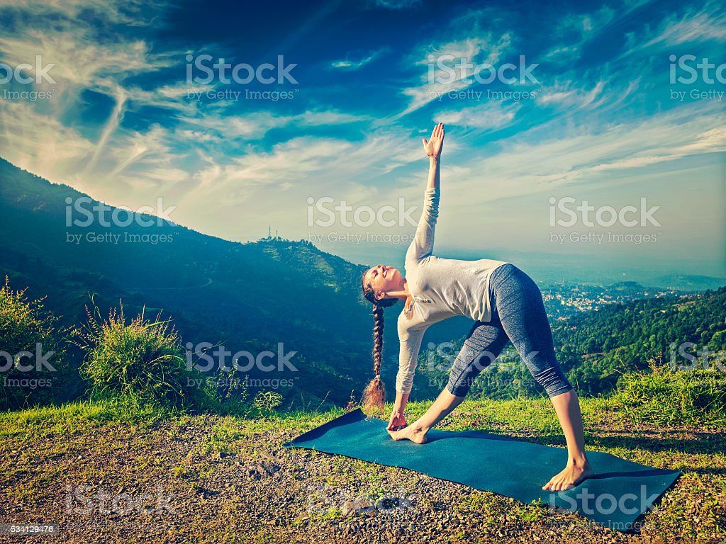 Woman doing Ashtanga Vinyasa yoga asana Utthita trikonasana stock photo