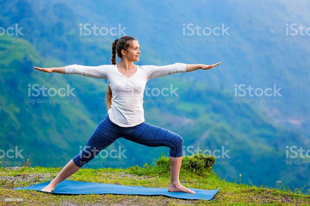 Woman doing Ashtanga Vinyasa Yoga asana Virabhadrasana 2 Warrior stock photo