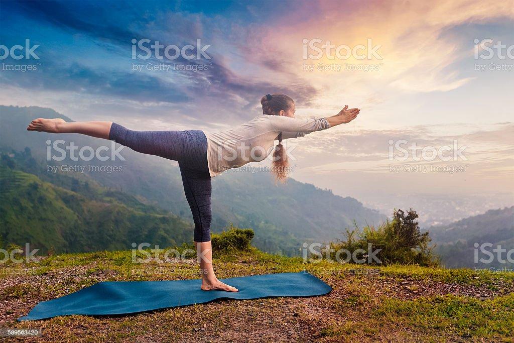Woman doing Ashtanga Vinyasa Yoga asana Virabhadrasana 3 Warrior stock photo
