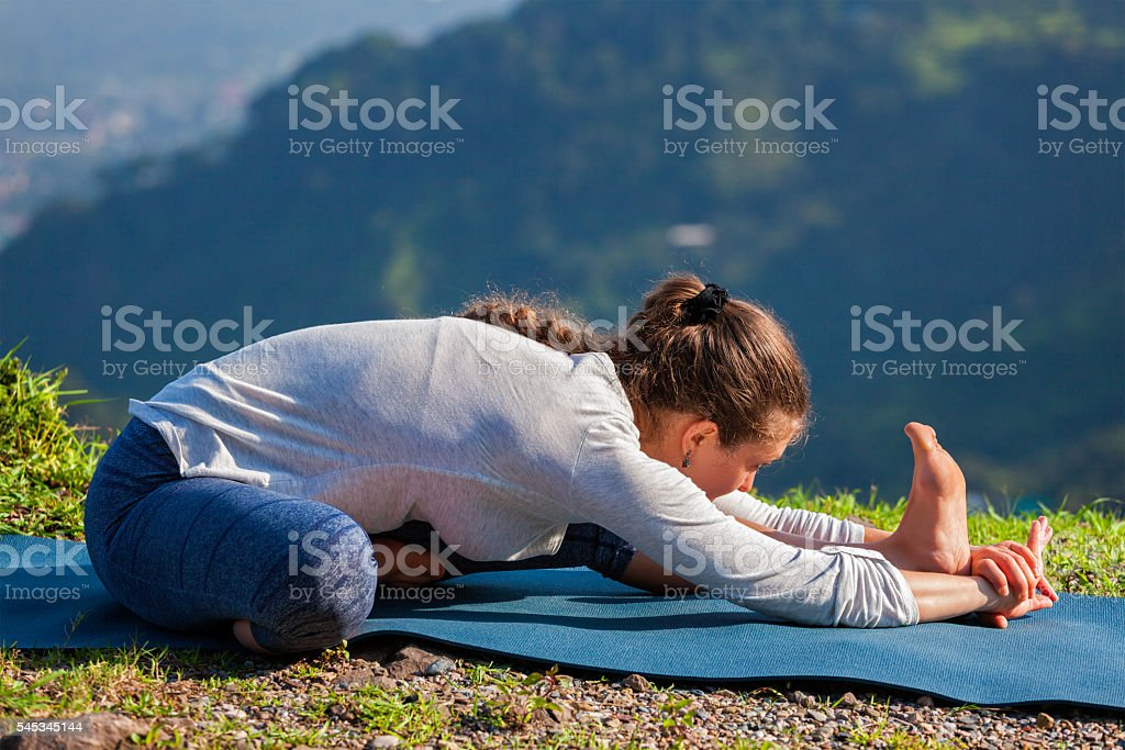 Woman doing Ashtanga Vinyasa yoga Janu Sirsasana A asana stretch stock photo