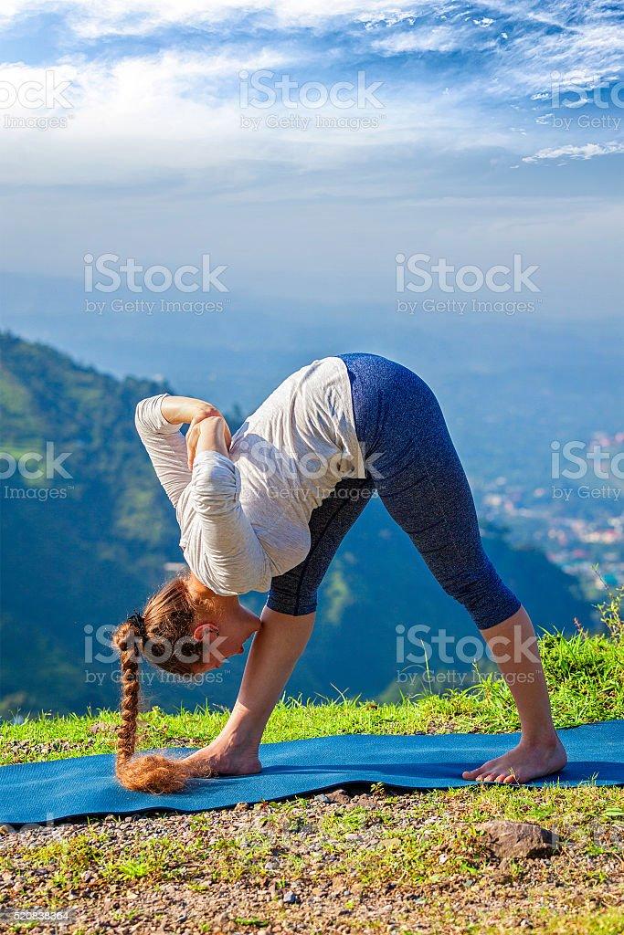 Woman doing Ashtanga Vinyasa yoga outdoors stock photo