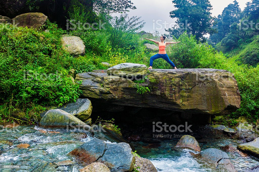 Woman doing Ashtanga Vinyasa Yoga Virabhadrasana 2 Warrior pose stock photo