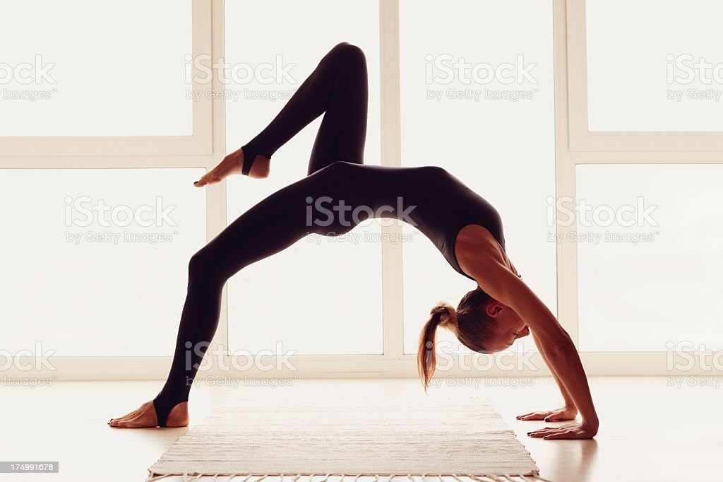 Woman doing back bend yoga pose with right leg bent in air stock photo