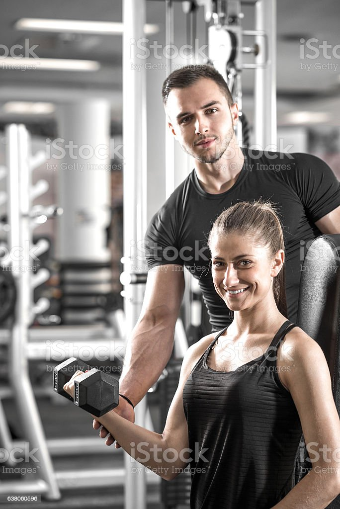 Woman doing bicep curls in gym with her personal trainer stock photo
