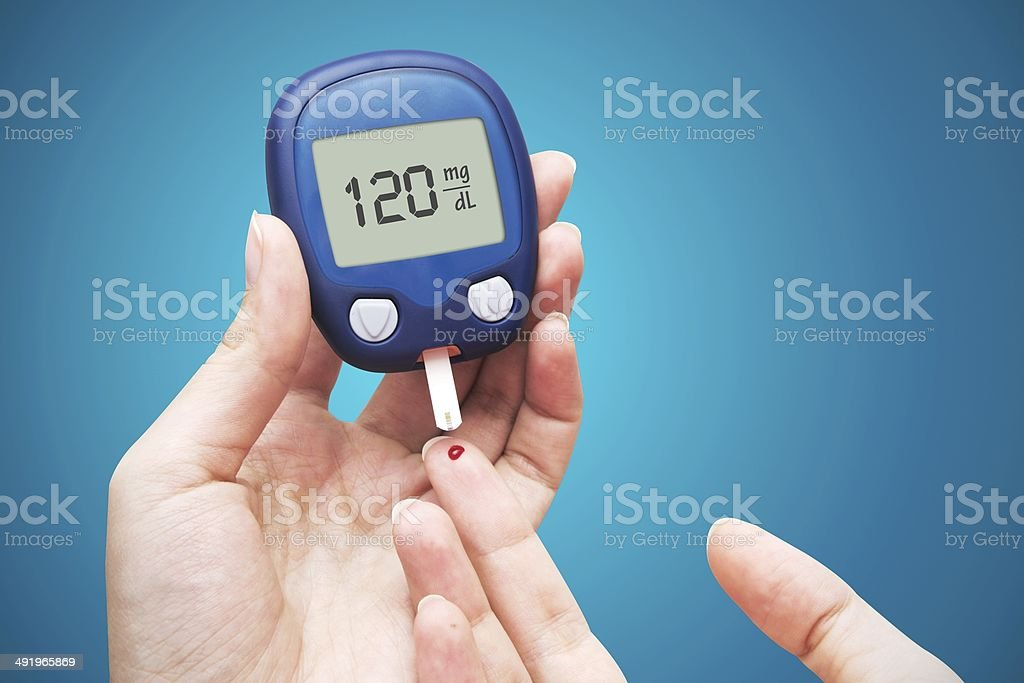 Woman doing blood sugar test stock photo