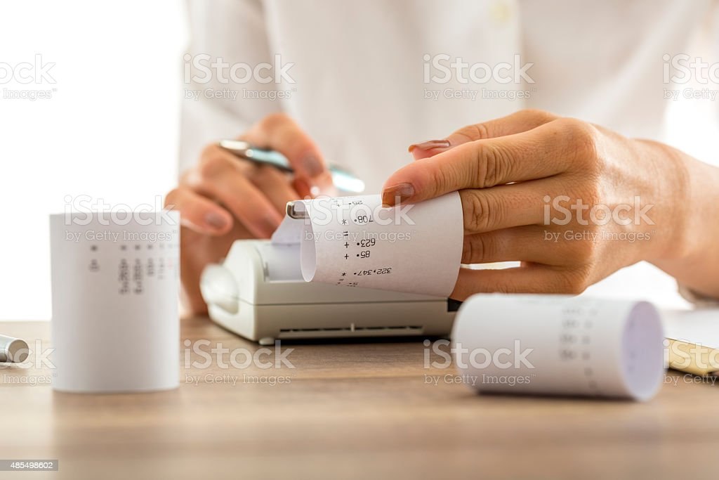 Woman doing calculations on an adding machine stock photo