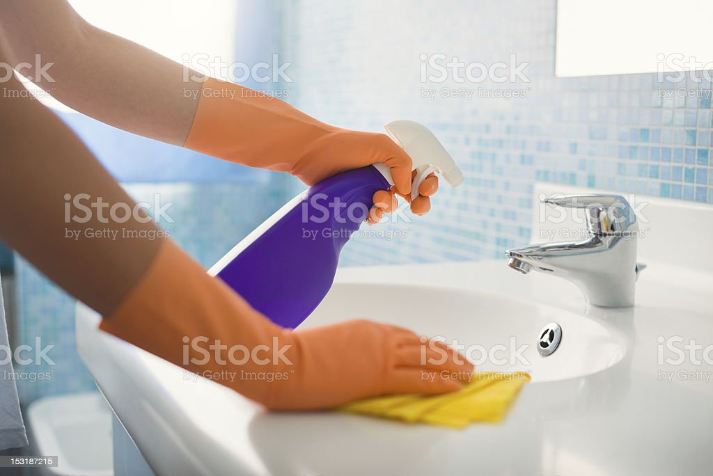 woman doing chores cleaning bathroom at home stock photo