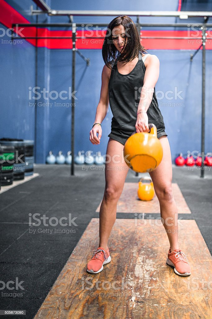 woman doing cross fitness exercise with kettlebell stock photo