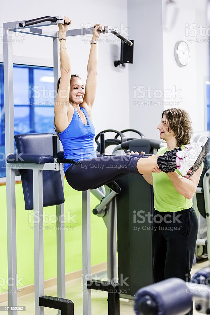 Woman doing crunch exercises with personal trainer royalty-free stock photo