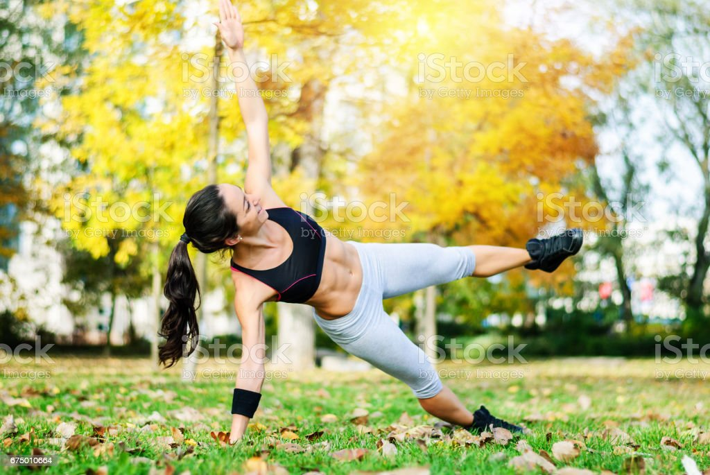 Woman doing exercises in the park stock photo