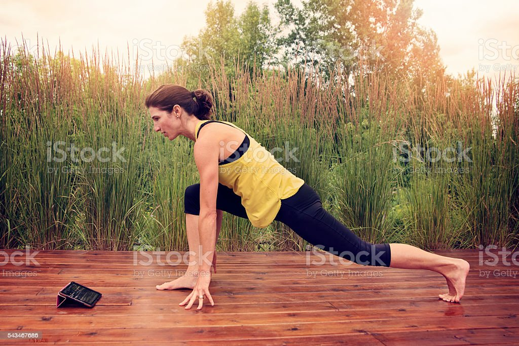 Woman doing exercises outdoors in summer with digital tablet. stock photo