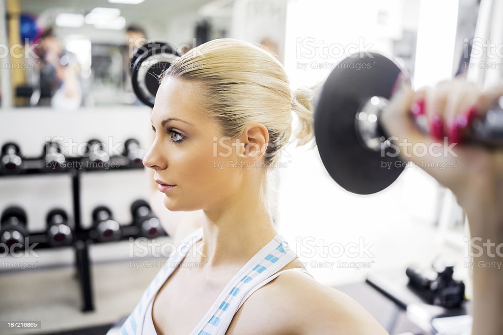 Woman doing exercises with dumbbells at gym. royalty-free stock photo