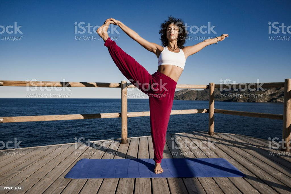 Woman doing Extended Hand To Big Toe yoga pose stock photo