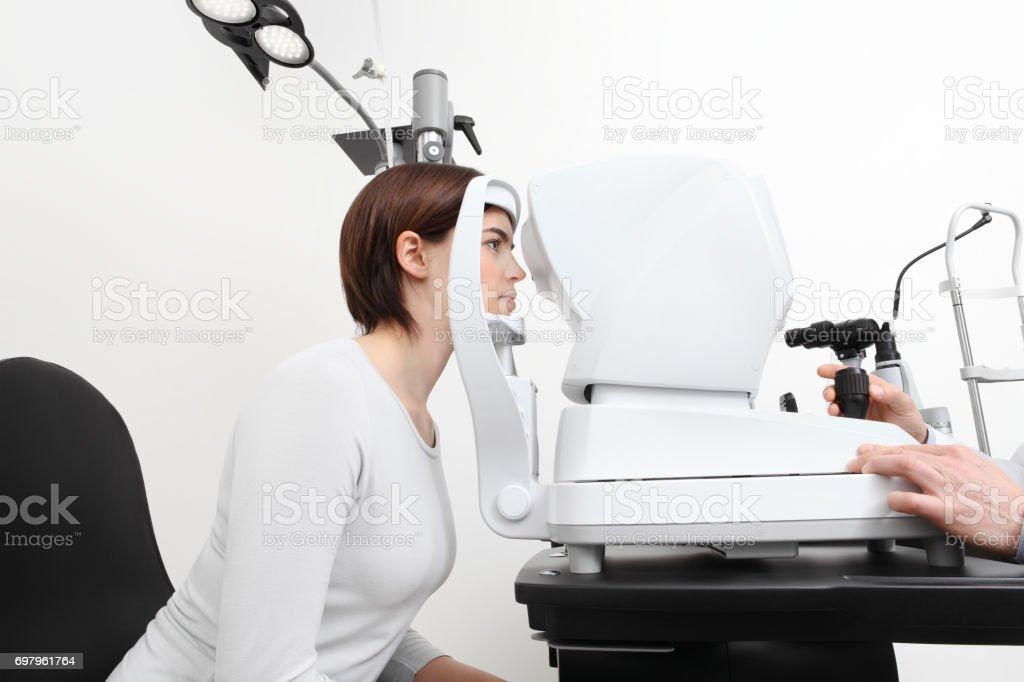 woman doing eyesight measurement with optician slit lamp stock photo