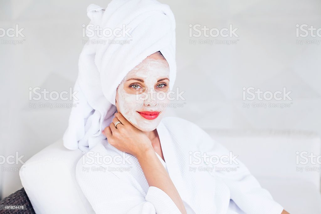 woman doing face mask at home stock photo