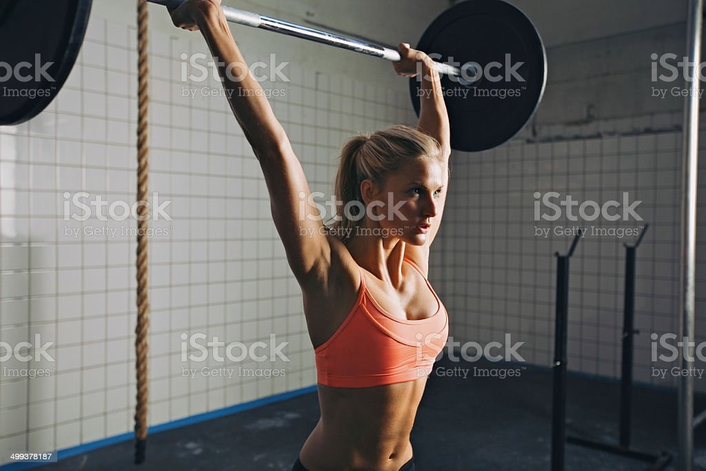 Woman doing gym barbell lifting stock photo