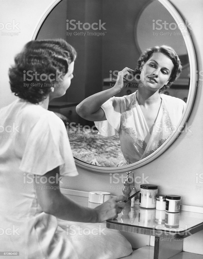 Woman doing hair in front of mirror, (B&W) royalty-free stock photo