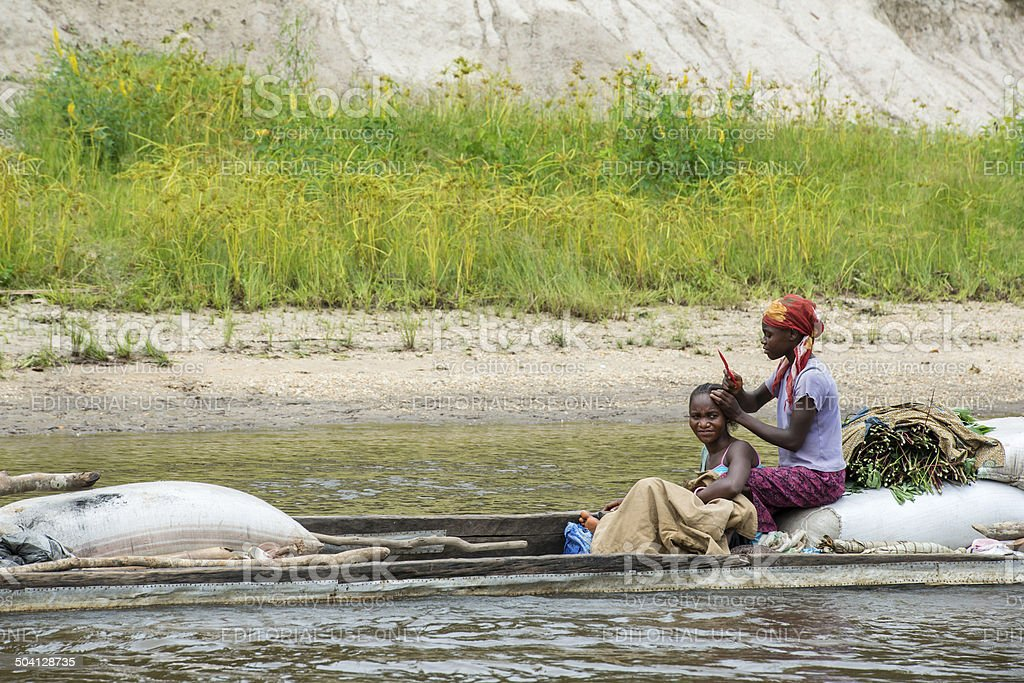 Woman doing hairstyling in a pirogue on the Congo River royalty-free stock photo