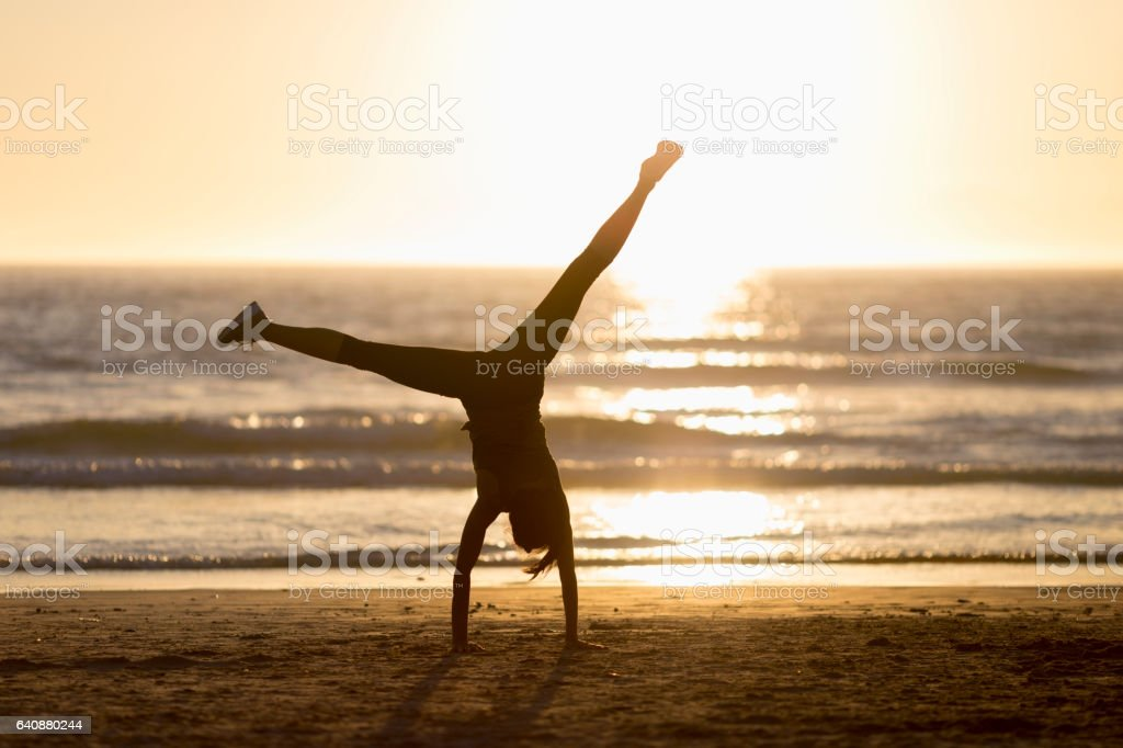 Woman doing handstand on shore during sunset stock photo