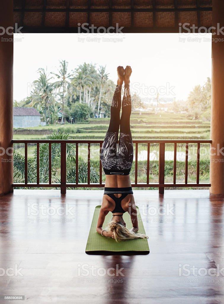 Woman doing headstand yoga pose stock photo