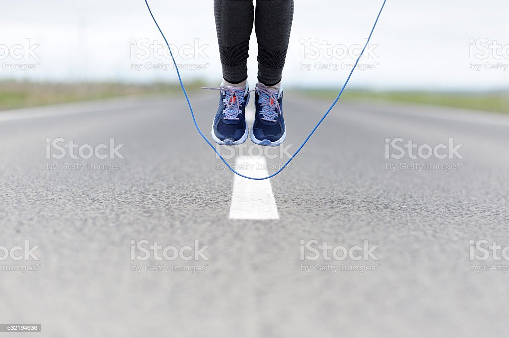 Woman doing jump roping on a sports field. stock photo