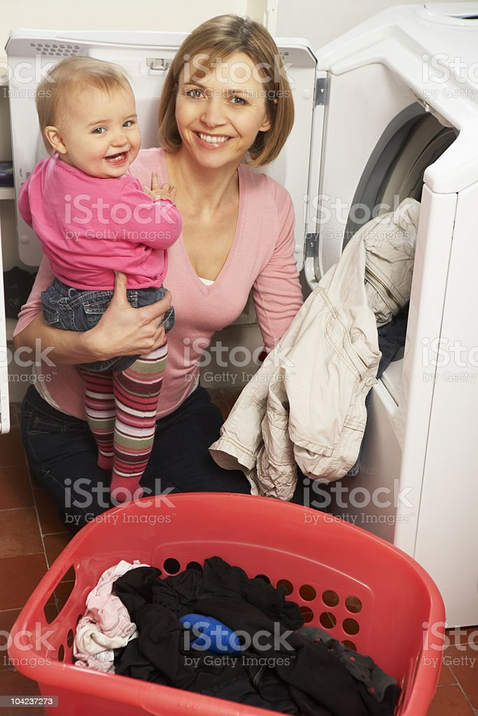 Woman Doing Laundry And Holding Baby Daughter royalty-free stock photo