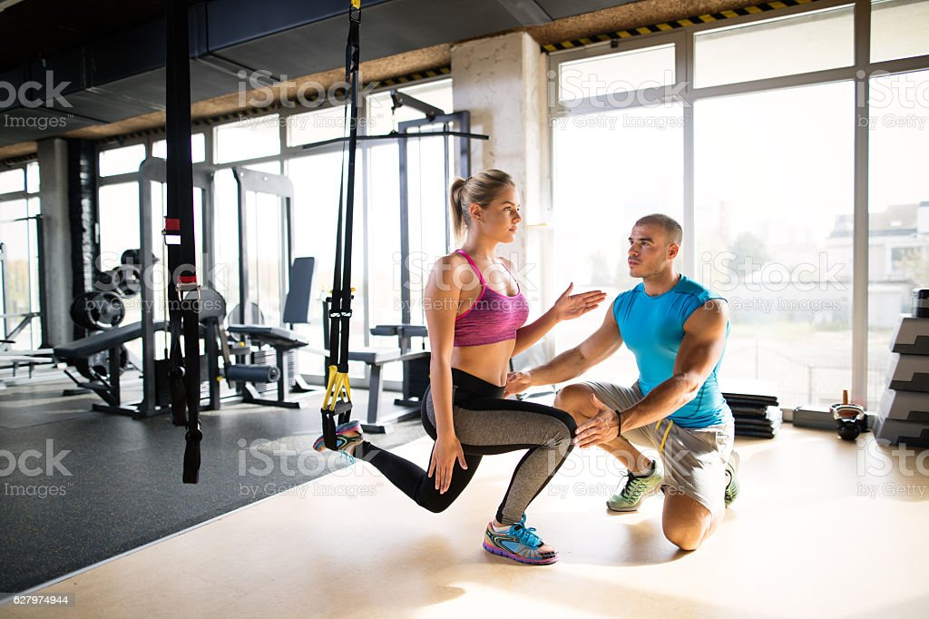 Woman doing leg exercises with suspension straps  at gym. stock photo