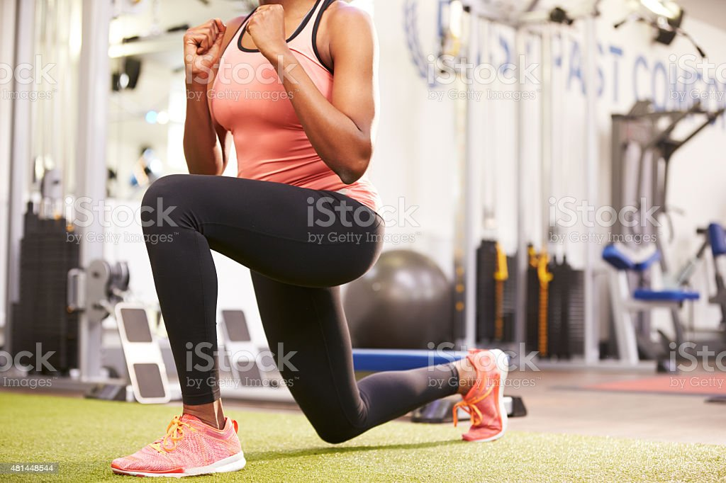 Woman doing lunges in a gym, crop stock photo