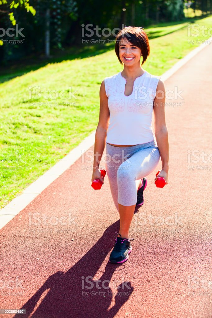 Woman doing lunges outside with weights stock photo