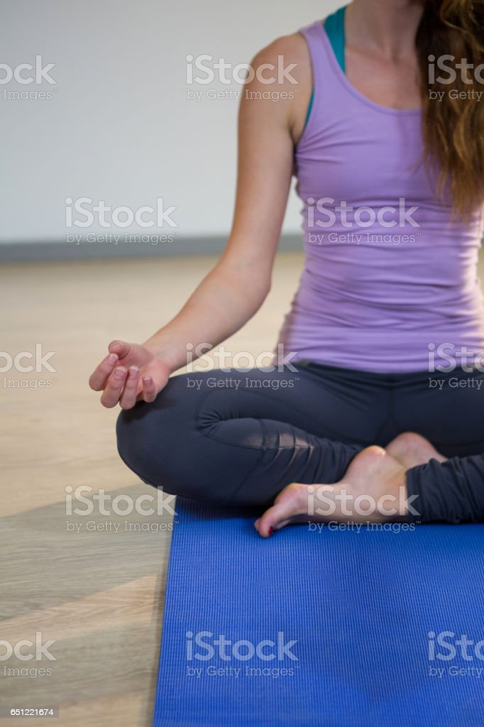 Woman doing meditation on exercise mat royalty-free stock photo