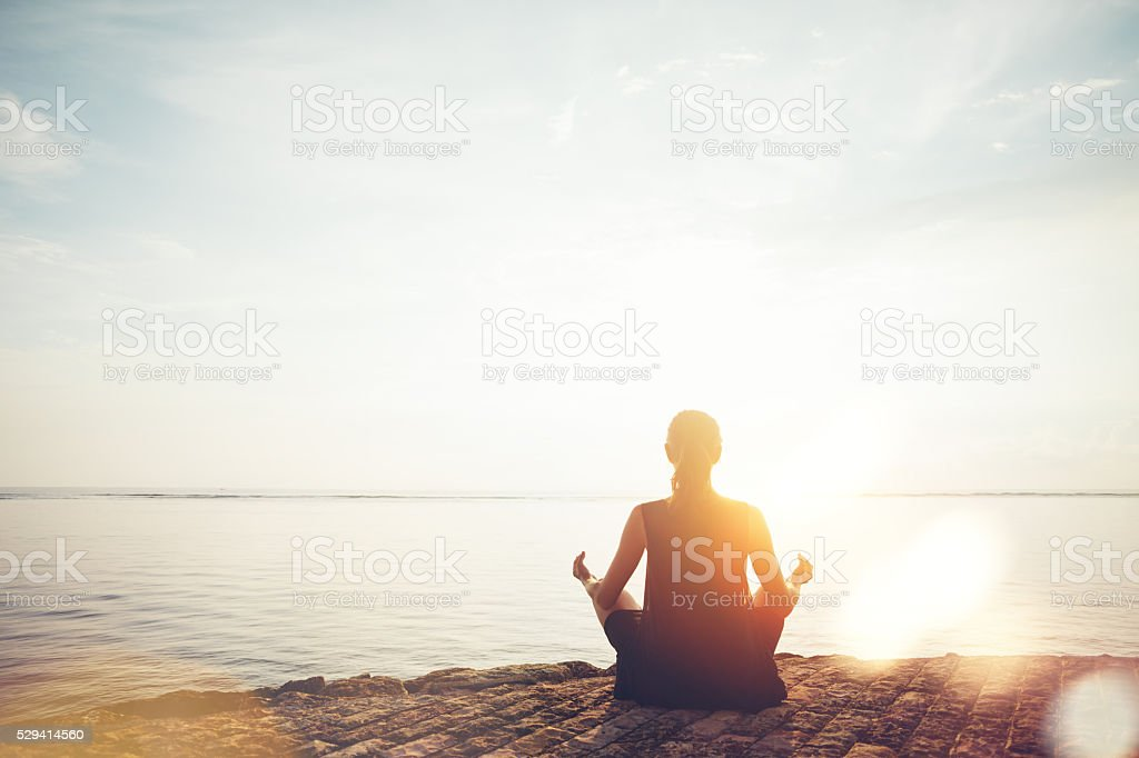 Woman doing meditation practice on the beach stock photo