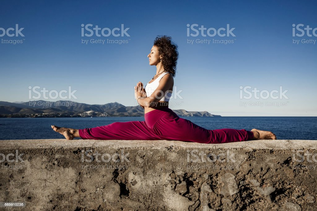 Woman doing monkey yoga pose stock photo