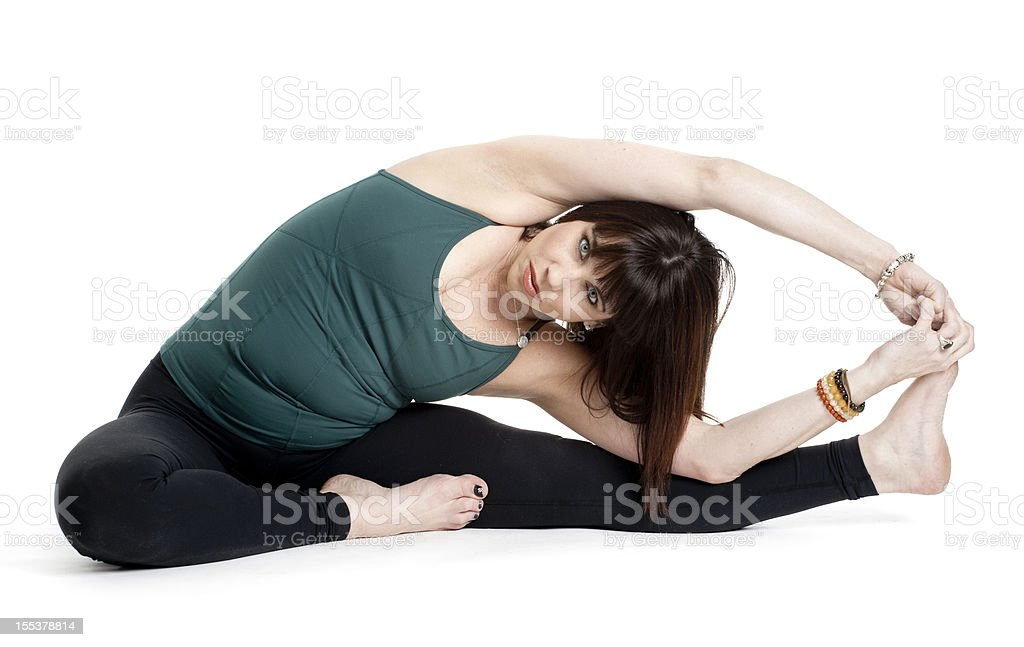 Woman doing Parivrtta Janu Sirsasana (revolved head-to-knee yoga pose) stock photo