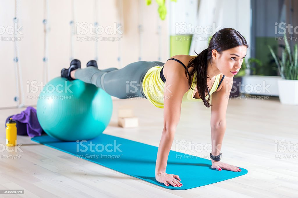 Woman doing pilates exercises with fit ball in gym or stock photo