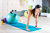 Woman doing pilates exercises with fit ball in gym or