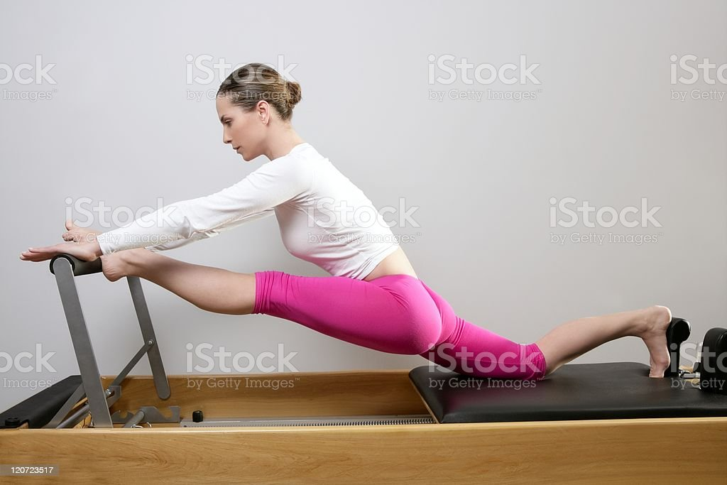 Woman doing Pilates stretching in reformer bed stock photo
