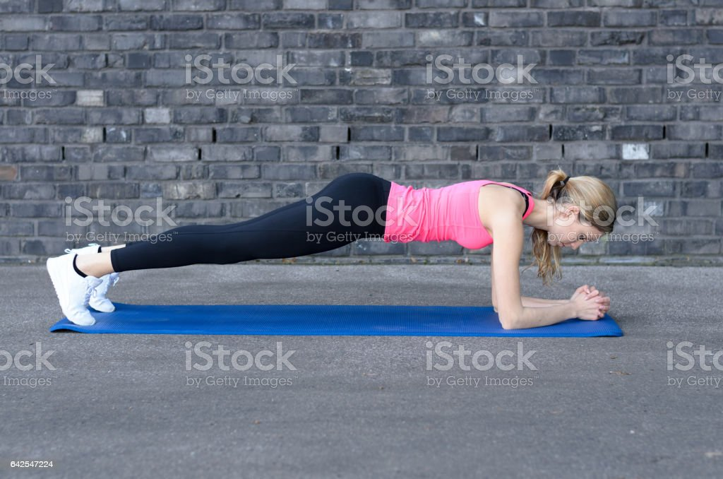 Woman doing plank while workout stock photo