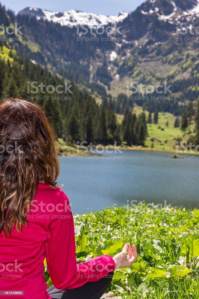 Woman doing prayers pose outdoor in nature stock photo