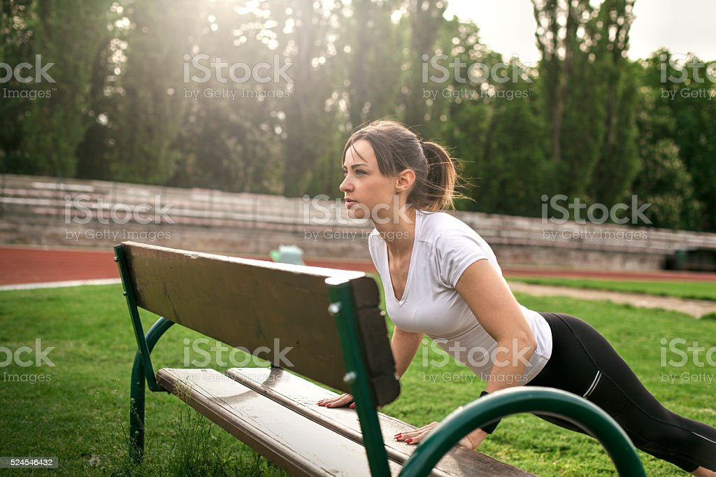 woman doing push ups exercise in outdoor workout stock photo