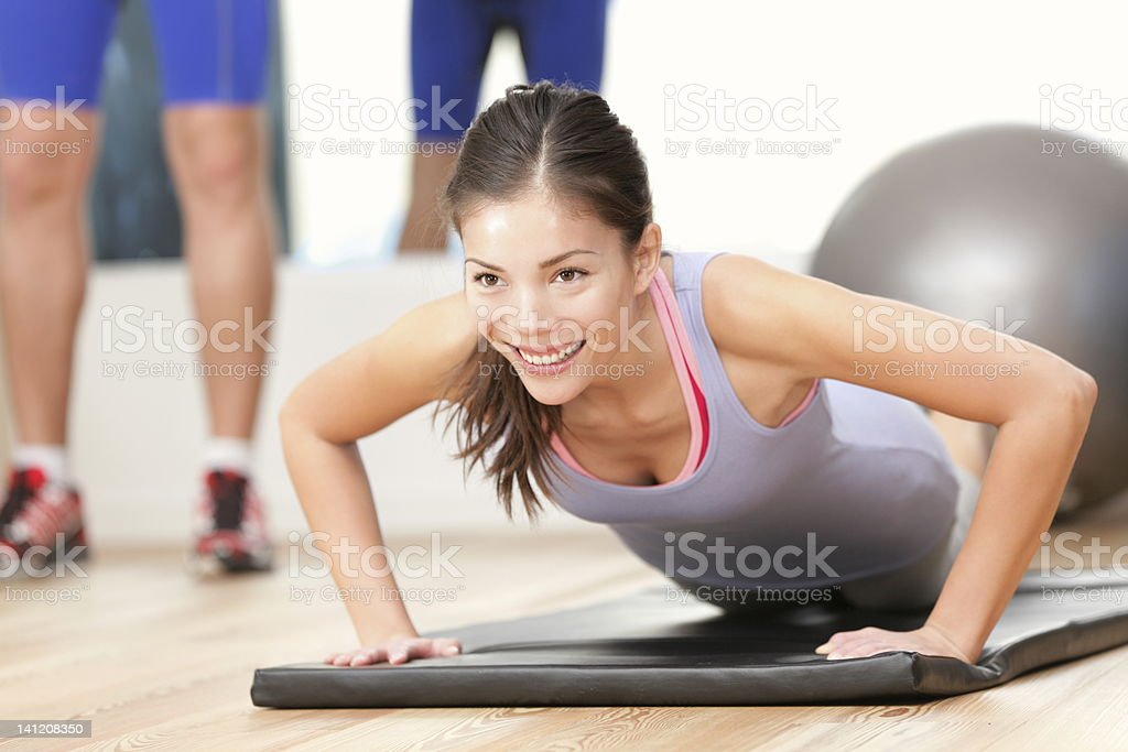 A woman doing push ups on a gym mat stock photo