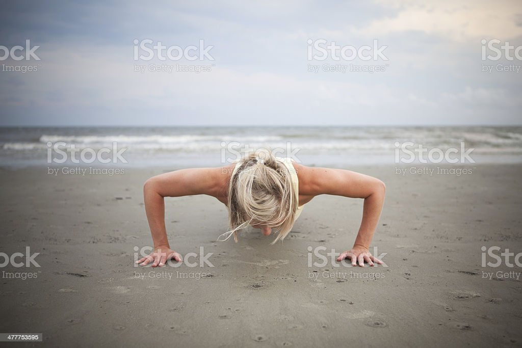 Woman doing push ups on the beach royalty-free stock photo