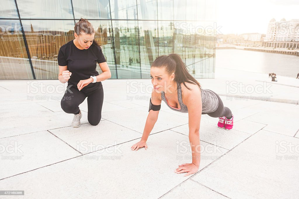 Woman doing push-ups exercises with her personal trainer stock photo