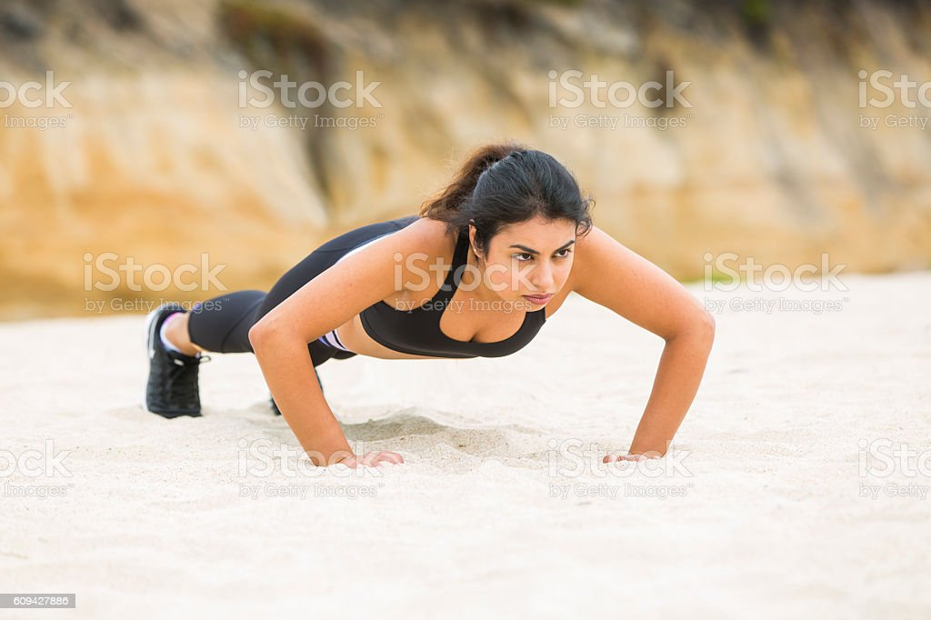 Woman Doing Push-ups on the Beach stock photo
