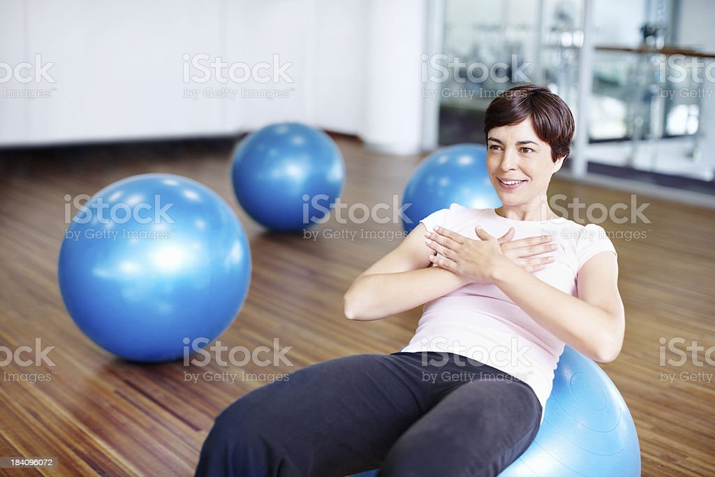 Healthy woman doing abdominal sit ups on exercise ball