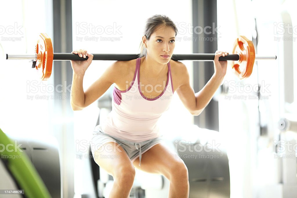 Woman doing squats in a gym royalty-free stock photo