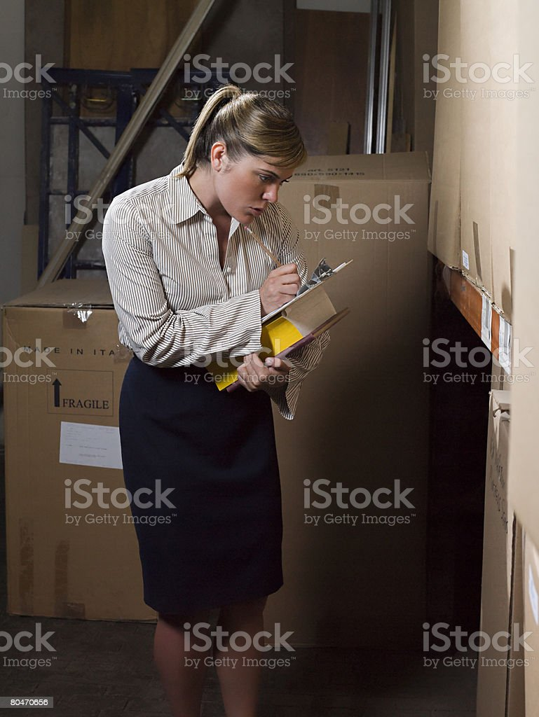 Woman doing stocktake in a warehouse stock photo